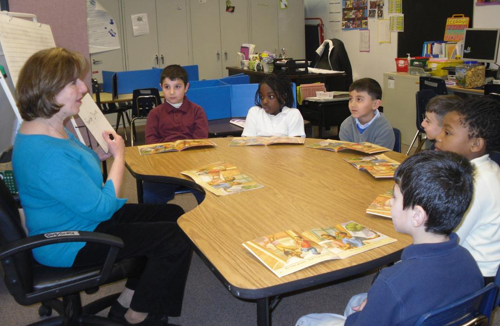 students working with teacher at table
